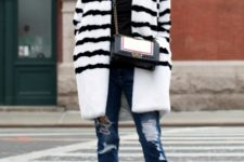 With black turtleneck, distressed jeans, white and black fur coat and chain strap bag