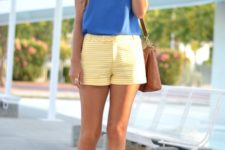 With blue sleeveless top, brown bag and golden platform sandals