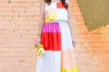 With color block top, sunglasses, yellow and white clutch and pink shoes