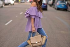 With distressed skinny jeans, beige bag and beige high heels