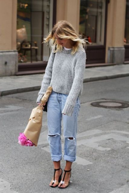 With gray sweater, bag and distressed jeans