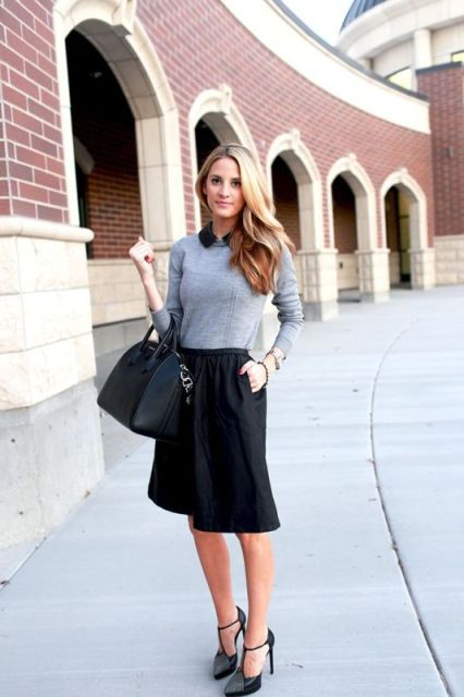 With gray sweater, black knee-length skirt and black bag