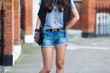 With gray t-shirt, black vest, black clutch and ankle boots