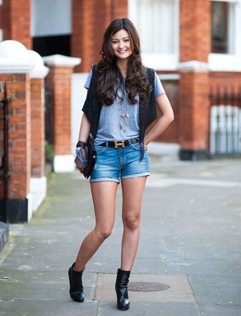 With gray t shirt, black vest, black clutch and ankle boots