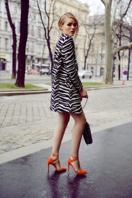 With orange high heels and black bag