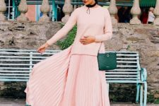 With pale pink long sweater and green bag