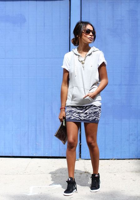 With printed mini skirt, clutch and black sneakers