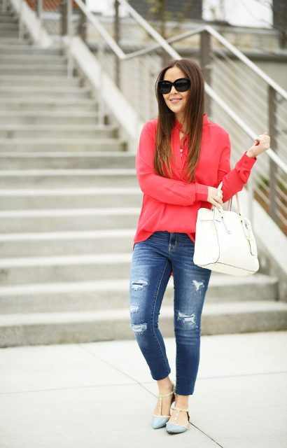 With red blouse, white bag and distressed jeans