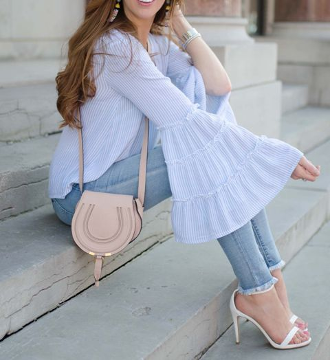 With skinny jeans, beige bag and white ankle strap high heels