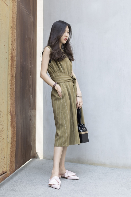 With striped belted midi dress and black bag
