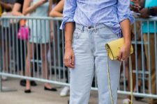 With striped shirt, yellow clutch and distressed jeans