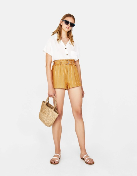 With white button down shirt, straw bag and white flat sandals