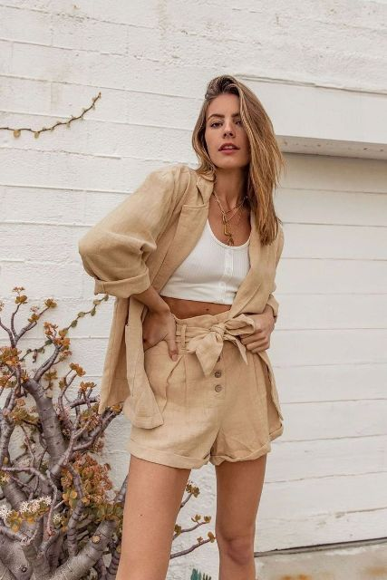 With white crop top and belted shorts