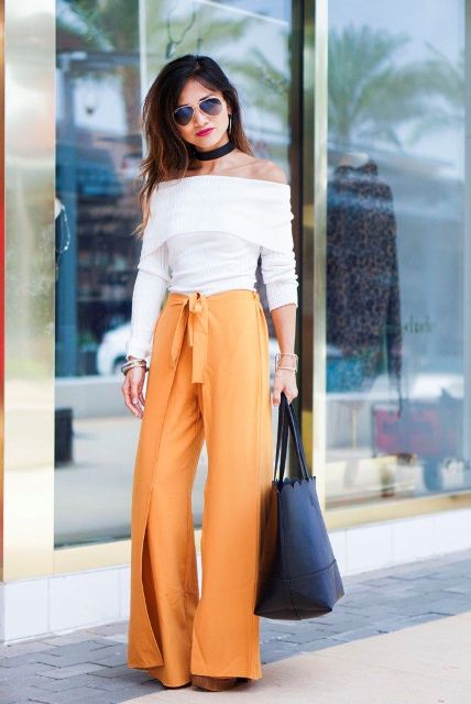 With white off the shoulder shirt, black tote bag and platform sandals