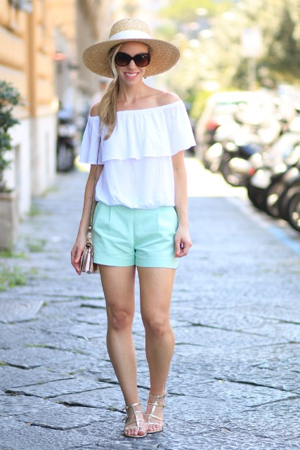 With white off the shoulder top, wide brim hat, mini bag and metallic shoes
