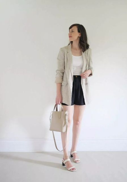 With white shirt, black shorts, beige bag and white sandals