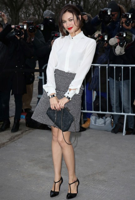 With white shirt, gray mini skirt and black bag