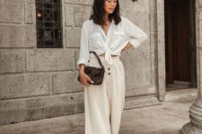 With white shirt, printed bag and black flat mules