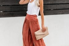 With white top, beige clutch and beige sandals