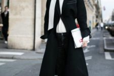 With white turtleneck, black midi coat, jeans and clutch