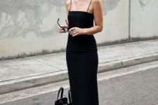 a black maxi fitting dress with thin straps, chic black slippers and a comfy black tote