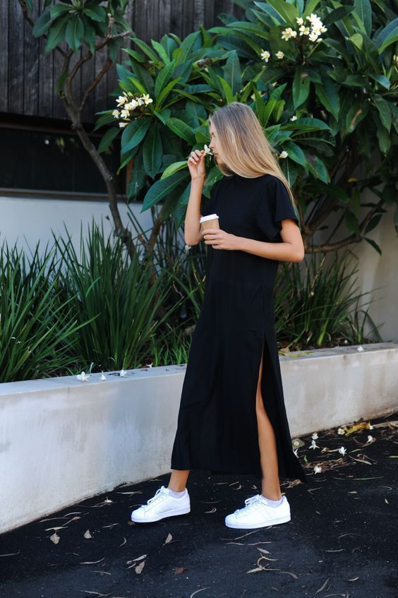 a black minimalist midi straight dress with a high neckline, short sleeves, side slits and white sneakers