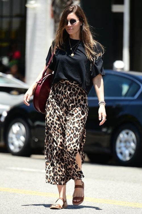 a black oversized tee, a leopard print midi skirt and tan Greek sandals plus a burgundy bag