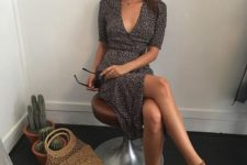 a black printed wrap mini dress, tan leather Greek sandals and a woven bag for this summer