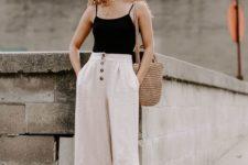 a black spaghetti strap top, neutral high waisted cropped pants, tan Greek sandals, a woven bag