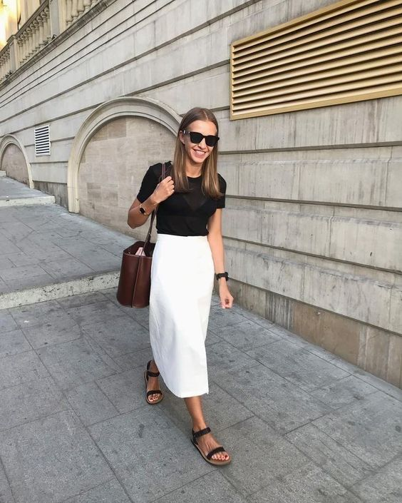 a black top, a white midi skirt, black sandals and a brown bag for a chic minimalist look