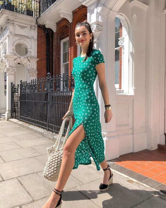 a bright green fitting midi dress with a high neckline, short sleeves and a side slit plus espadrilles and a woven bag