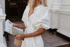 a cool white crochet lace wrap mini dress with a layered skirt and puff sleeves plus a basket bag