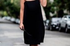 a minimalist black knee dress on thin straps, a hat and white sneakers for a hot day