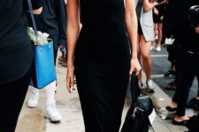 a minimalist black midi dress with open shoulders and sides, thick straps and black sneakers and a black bag