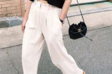 a minimalist outfit with an asymmetrical black crop top, white pants, a black bag and black Greek sandals