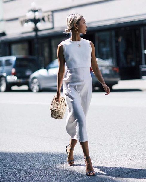 a minimalist white fitting midi dress with a high neckline, no sleeves, blue shoes and a basket bag