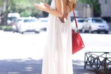 a minimalist white midi dress with spaghetti straps, a high low skirt and an open back, white sneakers and a red bag for a hot day