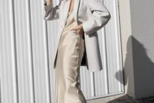 a neutral silk slip midi dress, a white oversized blazer and trainers for a trendy spring to summer look