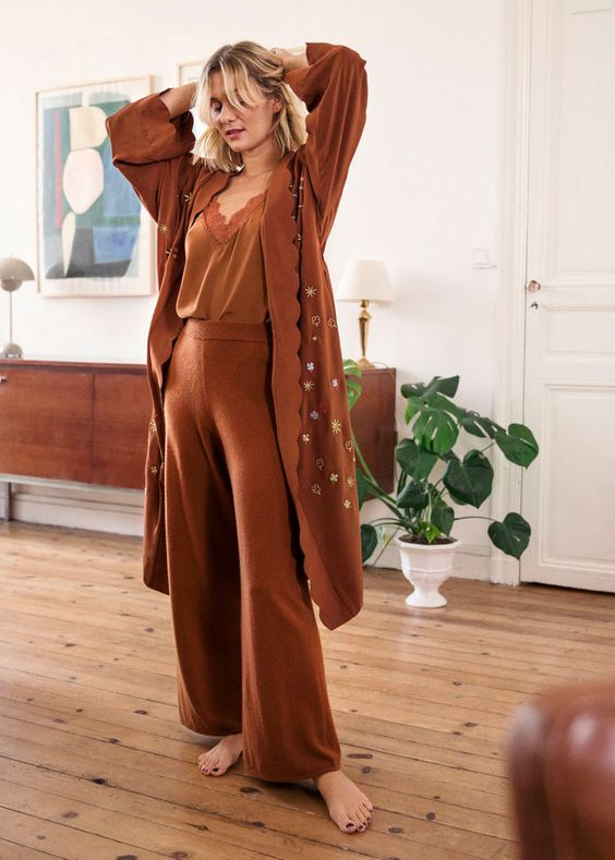 a rust colored loungewear suit with a lace neckline top, wideleg pants and a long robe with a star print