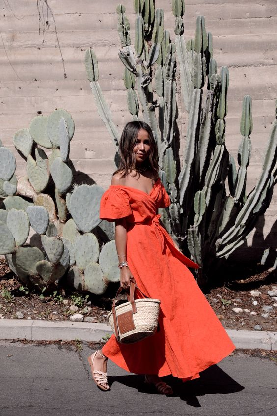 a rust colored off the shoulder A line linen maxi dress, white Greek sandals and a woven bag for summer
