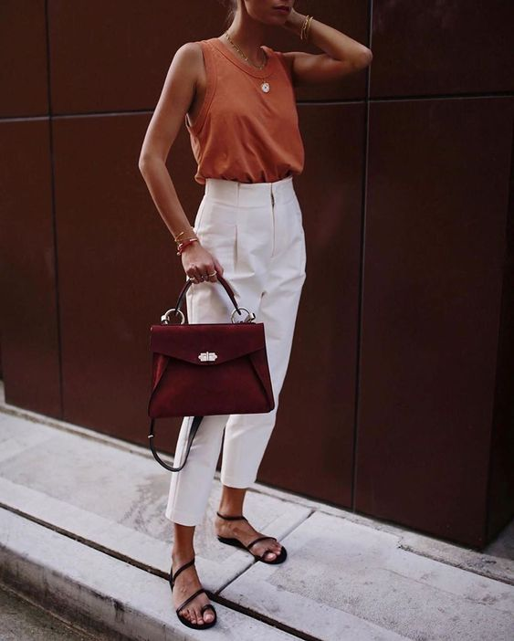 a rust-colored top, white high waisted pants, black sandals and a burgundy bag