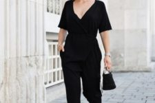 a summer party or work look with a black jumpsuit with a deep neckline, short sleeves, a black bucket bag and Greek sandals
