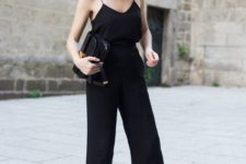 a total black look with a spaghetti strap top, pants, chic slippers and a crossbody bag