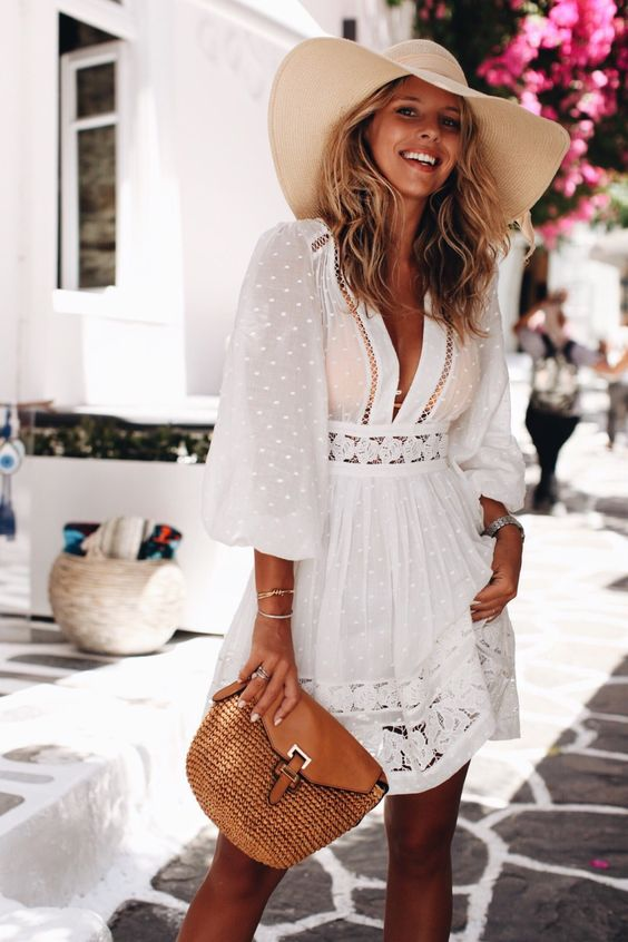 a vacation white mini dress with long puff sleeves, a deep plunging neckline and lace skirt, tan shoes and a bag