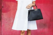 a white A-line knee dress with a high neckline and short sleeves, white loafers and a black bag