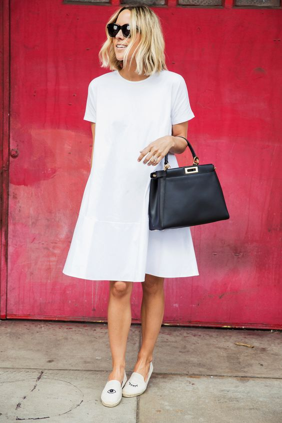 a white A line knee dress with a high neckline and short sleeves, white loafers and a black bag