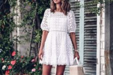 a white lace mini dress with a high neckline, puff sleeves and lace up sandals plus a basket bag