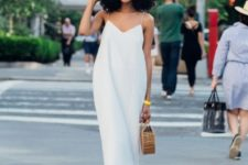 a white midi minimalist dress with spaghetti straps, white slippers and a wooden bag for summer