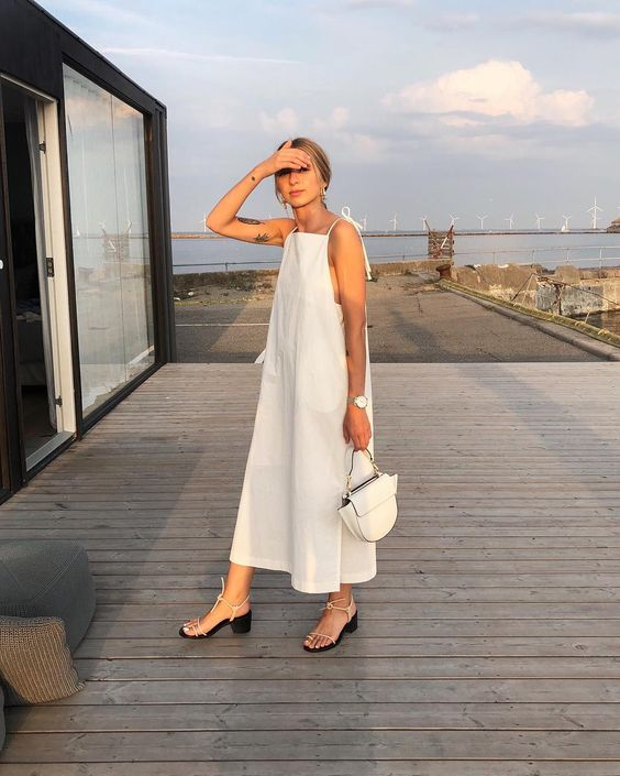 a white minimalist A-line midi dress with thin straps, open shoulders and sides, a catchy white bag and lace up shoes