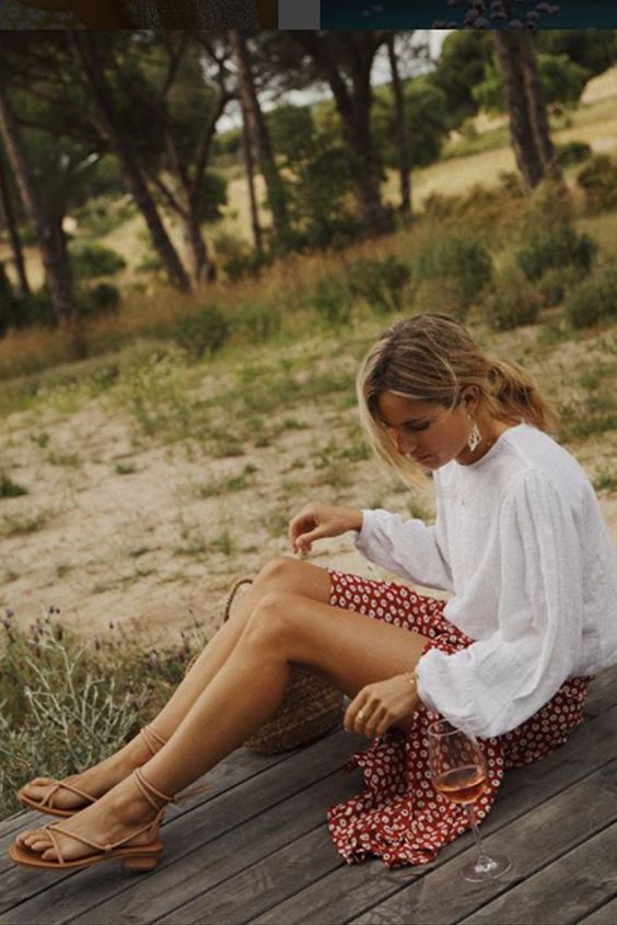 a white oversized shirt with puff sleeves, a red printed skirt and tan Greek sandals for summer